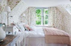 A cozy, wallpapered, attic bedroom.