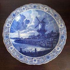Porceleyne Fles - Grote schotel met De molen van Wijk bij Duurstede naar Jacob van Ruisdael  Een imposant groot sierbord van de Porceleyne Fles.Met de hand geschilderd in diep Delfts Blauw. De afbeelding is naar een schilderij van Jacob van Ruisdael: De molen bij Wijk bij Duurstede.Het originele schilderij hangt in het Rijksmuseum te Amsterdam en is omstreeks 1668/1670 geschilderd.Het tafereel is mooi zeer fijn afgewerkt met diepe blauwe kleuren. Vervaardigd in 1953 (jaarletters BX)…