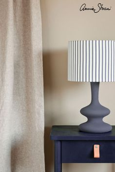 Side table painted with Chalk Paint® furniture paint by Annie Sloan in Oxford Navy, an inky, traditional navy blue which evokes the strong, august blue of academic insignia and fountain pens, as well as the rich pigment indigo blue so synonymous with traditional Indian block printing. With white wash floorboards and wall painted with Country Grey. Curtain made from Linen Union in Old White + French Linen, lamp base painted with Old Violet and lampshade made from Ticking in Old Violet.