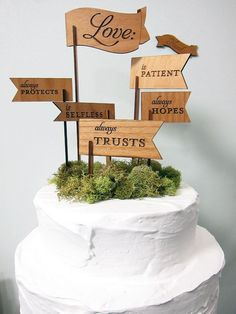 These wooden cake toppers add a personal touch to a wedding cake with unique little wooden flags listing the attributes of love.