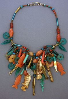 Necklace | Anna Holland. A fun collection of bone, bronze, and carnelian fish pendants which Anna has brought together from all over the world. Combined with an assortment of glass and carnelian beads and bronze charms.