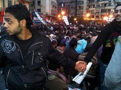 8. This image from the Egyptian uprising: Christian protesters protect Muslim protesters during their prayer time.