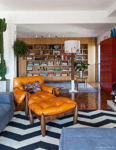 Sala de estar com estante de madeira feita sob medida e poltrona mole de Sérgio Rodrigues.
