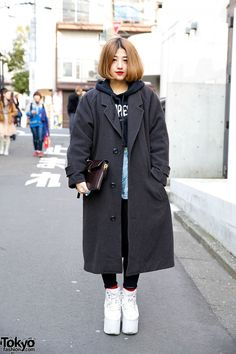 This is Tianba, a 24-year-old student we met in Harajuku. She is wearing denim shorts with black tights and a Dimepiece LA hoodie, under a resale coat. The clutch is Alexander Wang, the flatforms are YRU, and the ring is Alexander McQueen. (Tokyo Fashion, 2014)