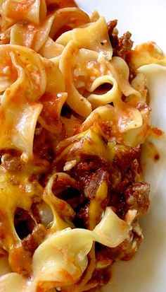 Kinda Creamy Pasta Bake...     1 to 1 1/4 pound ground beef     1 can (about 15 oz) tomato sauce     1/2 teaspoon salt     black pepper     8 ounces egg noodles (I use one regular sized package)     1/2 cup sour cream     1 to 1 1/4 cup cottage cheese     1/2 cup sliced green onions     1 cup grated cheddar cheese