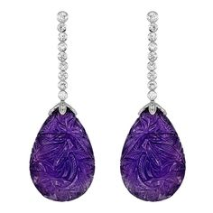 Floral Carved Amethyst Diamond Drop Earrings, Estate 18 karat white gold drop earrings consisting of 18 bezel set full cut diamonds, 9 in each earring, set in a vertical row having an estimated total weight of .85 carats with 2 tear drop shaped floral carved amethyst, measuring approximately 32 x 20.30 mm and accented with pave set diamond caps. 1stdibs.com