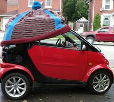 A Smart car. Cheap to insure (if anything is...) but not sure about the hat if I'm honest! > I think GUS should have one of these hats!