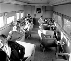 """""""This is the Tourquoise Room lounge car on the Santa Fe's Super Chief. No other railroad seemed to have thought of turning the easy chairs around so you could look out the windows and people walking down the aisle wouldn't stumble all over your feet! If the passengers look relaxed and serene, can you think of a better way to spend a day and a half getting from Los Angeles to Chicago? Of course, you could save some time by flying, but … Can we bring back 1953?"""""""