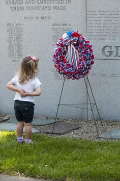 Two-year-old Samantha Presti shows respect for the wreath placed at Abington's All War Memorial during the Memorial Day Ceremonies on Monday, May 28, 2012. K.A. MacDonald/Wicked Local Abington