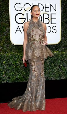 Golden Globes 2017  WHO: Chrissy Teigen WEAR: Marchesa metallic lace fishtail gown with halter neck, sculptural peplum, and floral embroidery; Jimmy Choo Carmen clutch.