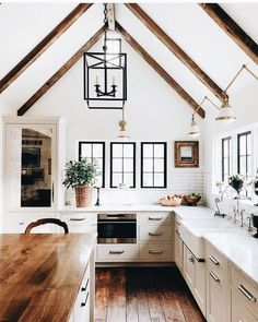 An all-white kitchen gets a supersize dose of warmth with wood island top, beams and floors.