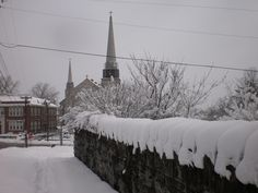 Sidewalk, wall and church in the snow.