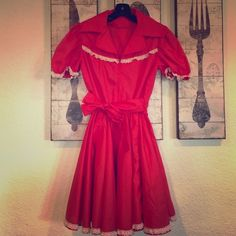 """Vintage red twirl dress Red twirly dress with lace trim across chest, at sleeves and hem. Zipper front closure, attaches sash tie at waist. Elastic waist from 10""""-11"""" max across, 34"""" from back neck to hem Vintage Dresses"""