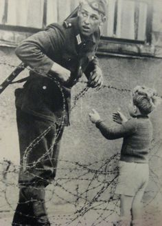 """Berlin, August 1961, the anniversary of the building of the Berlin Wall. With obvious apprehension, a young East German soldier glances about as he prepares to let a small boy pass through the emerging barrier. No doubt the boy spent the night with friends and found himself the next morning on the opposite side of the Wall from his family.  The soldier was seen by a superior officer who immediately detached him from his unit. """"No one,"""" reads the inscription, """"knows what became of him."""""""