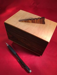 This well-crafted small wooden box measures 5-5/8 W x 3-1/2 D x 3-1/4 H. The sides are Bocote, from Central America. The top and bottom are Hard Rock Maple, from North America. The handle is Brasilian Canarywood.  As with all of our boxes, this one is finished with several coats of Tung Oil and then a combination of Orange Oil and Beeswax is rubbed in. A small container of Tung Oil is included so you can keep the finish fresh.  Small wood boxes make wonderful gifts. And the recipient always…