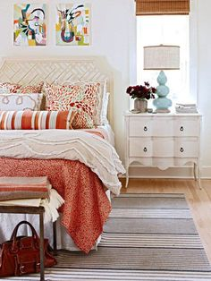 Both fabric and art work together to dictate a bedroom's fabric and accessory choices below. Notice those Pine Cone Hill pillows have shades of apricot, deep orange, and pale aqua blue. Mixed into this space are two different stripes in blues and oranges on the rug and bolster pillow, and a quilt in a smaller scale coral motif, all in the same palette present in the artwork and decorative pillow fabric.