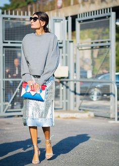 A gray sweatshirt is spiced up with gold hoop earrings, a colorful clutch, sequined slit skirt, and strappy metallic heels