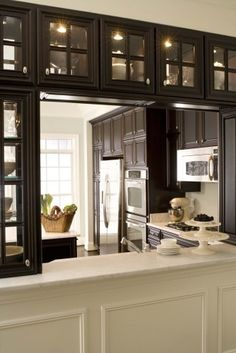 kitchen pass-through, cabinets with double sided glass doors makes it more open while not giving up storage space