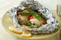 Grilled-Fish Foil Packets Fancy rolled-up fish fillets topped with asparagus and peppers cook up quickly and deliciously wrapped in foil packets with lemons for the grill. Fish In Foil Packets, Foil Packet Dinners, Foil Pack Meals, Foil Dinners, Grilling Recipes, Fish Recipes, Seafood Recipes, Dinner Recipes, Cooking Recipes