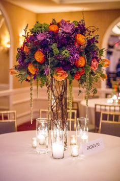 Purple and orange fall arrangement. Branching Out Floral & Event Design Photography: Amy Herfurth Photography - www.amyherfurth.com  Read More: http://www.stylemepretty.com/texas-weddings/2014/01/15/colorful-rosewood-turtlecreek-mansion-wedding/