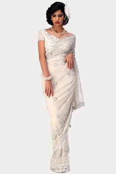 A beautiful, delicately embroidered floral lace look saree, concocted with georgette with ornamental borders and very fine tonal work with highlighting by pearls and stones and sprinkling of jewel butis, comes with a white ornamental blouse.