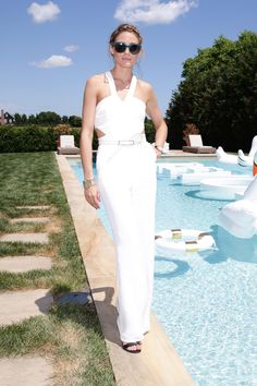 Olivia Palermo in a white Lovers + Friends halter jumpsuit and blue sunglasses at Revolve in The Hamptons