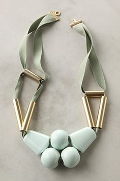 """$378 Collier Pistache Necklace  Immense ceramic pearls and fans of pale green dangle below gleaming, brushed-brass tubes and soft cording. Handmade in France by Marion Vidal.  Hook clasp  Ceramic, brass, polyester  22.5""""L  5"""" bib  Handmade in France"""