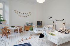 All-white kids' room with twin iron frame beds.