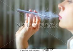 Closeup portrait of female smokers. She smokes electronic cigarette against a blurred background. Concept: safe way of smoking, how to stop smoking - stock photo Stop Smoke, Blurred Background, Electronic Cigarette, Smokers, Close Up, Holding Hands, Hair Accessories, Concept, Stock Photos