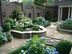 Sculptured fountain in an enclosed courtyard and blue hydrangeas.
