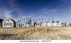 Brightly coloured row of beach huts on Mudeford Spit near Christchurch in Dorset - stock photo