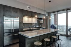 Luxury contemporary kitchen with dark wood cabinets with European pull hardware, Edison style pendant lights, large dining island and viking appliances