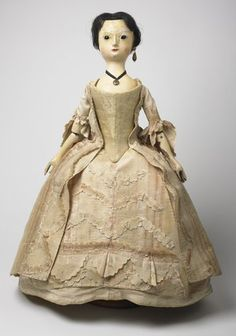 'The Queen of Denmark' doll: c.1760. Wearing a sack dress with matching petticoat of pink and yellow figured Spitalfields silk and pink silk stays. Believed to have been given by an English princess to Elizabeth, daughter of Thomas Sampson, Chaplain of the Royal Hospital at Chelsea.