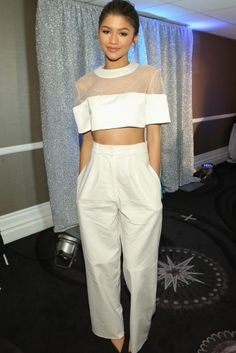 Zendaya has been our newest fashion obsession and you can clearly see why. The actress shows off her figure in a cropped sheer top and a pair of chic wide-leg pants.
