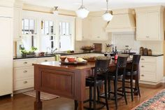 Ivory cabinets, framed beadboard backsplashes, quartersawn oak flooring, and a table-style island give this open kitchen an inviting period vibe. | Photo: Laura Moss | thisoldhouse.com