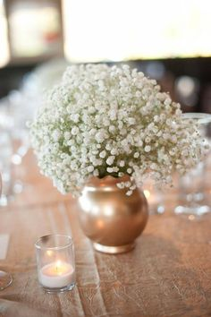 The bride spray painted thrift store vases gold and filled them with baby's breath for a breathtaking centerpiece. LOVE.