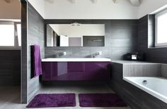 Ultra modern bathroom design with grey walls and floor and deep purple accents