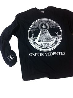 "a black longsleeve shirt, with our own variation of the all seeing eye. our signature ""i"" logo will be on the sleeve as always, with a full chest print of our all seeing eye pyramid and the words ""OMNES VIDENTES"" which is Latin for ""all seeing"""
