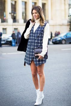 Helena Bordon layers a turtleneck underneath a plaid vest dress and pairs it with white ankle boots.