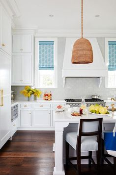 White kitchen features white stacked cabinets adorned with brass hardware paired with white quartz countertops and a concrete gray subway tile backsplash.