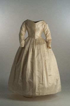 1842 Wedding dress on satin silk. Gathered decorations on shoulders for a draped effect on the bust. Museo del Traje.