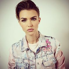 Ruby Rose wears a slicked back hair style with smokey eye makeup and nude lips.