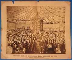 """""""SOLDIERS' FAIR, at Springfield Mass., December 22, 1864"""". Pub. by photographer J.C. Spooner of Springfield in 1865. Photo: 15 3/4"""" x 19 3/4"""". Matt: 19 3/4"""" x 23 3/4"""". Photomontage features Gov. Andrew. Spooner published an index to the photograph (which the Boston State Library owns) but the photograph itself does not appear in OCLC."""