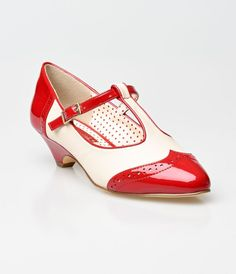Consider us captivated, dames! A kittenish pair of matte pointed toe pumps, these retro red and cream faux leather spectator heels are whimsy personified! Equipped with dainty brogue detailing over the wingtip style vamp, an adjustable and elasticized T-s