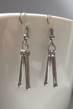 Do you play drums? Or do you like Whiplash movie? If yes, these silver dangle drumstick earrings are for you. Cute, delicate, aesthetic, music gift or accessories for you rock or pop or heavy metal or any music outfit #drumstick #drumstickearrings #dangleearrings #musicgift #drumset #drummergirl #drummer #musiciangift #rockjewellery #festivalfashion #festivaloutfit Girls Earrings, Unique Earrings, Unique Jewelry, Punk Rock Festival, Grunge Accessories, Play Drums, Musician Gifts, Designer Earrings, Small Businesses