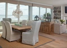 Coastal Dining room with shell chandelier and slipcovered chairs. #Diningroom #CoastalInteriors #Shellchandelier #slipcoveredchairs AGK Design Studio.