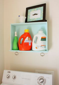 Laundry room shelf made from a painted drawer. Functional! & I like the drawer hardware, makes for great decoration & useful for hanging small things (an extra set of keys, perhaps)!
