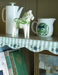 Green and white dala horse, green cat pitcher, tall white pitcher, scalloped shelf border
