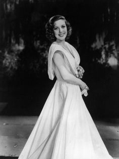 American leading lady Loretta Young wearing a large smile and a flowing evening dress c1936