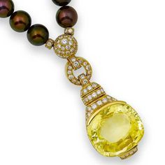 A yellow sapphire, diamond and cultured pearl pendant/necklace, by Cartier  The pendant set with a large cushion-shaped yellow sapphire beneath an articulated buckle-shaped surmount pavé-set with brilliant-cut diamonds, suspended from a slightly graduated single-strand cultured pearl necklace, the 8.0-8.9mm., cultured pearls of aubergine tint, highlighted at intervals with pavé-set brilliant-cut diamond roundels and spheres, diamonds, yellow sapphire untested, signed Cartier